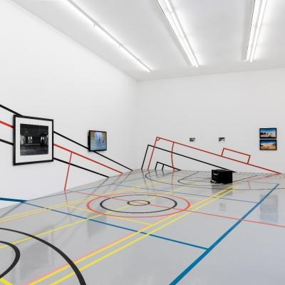 """Céline Condorelli, """"Limits to Play"""", 2020, widok instalacji, FRAC Lorraine (Francja), fot. Fred Dott, dzięki uprzejmości artystki: Fotografia prezentuje widok wystawy. W centralnej części ekspozycji znajduje się powierzchnia, pełniąca funkcję boiska. Przestrzeń została podzielona za pomocą linii na strefy w kolorystyce czerni, czerwieni, niebieskiego oraz żółtego. Na białych ścianach w anturażu kolorowych granic widnieją artefakty takie jaki fotografie oraz ekrany wyświetlające video."""