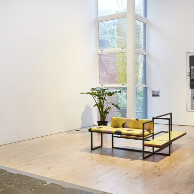 """Céline Condorelli, """"Average Spatial Compositions"""", 2015, installation view, Prologue, Stanley Picker Gallery (Kingston), photograph by Corey Bartle-Sanderson, courtesy of the artist.: The photo shows a fragment of the exhibition view. In the foreground, there is an object resembling a piece of furniture. In the background, there is a photo placed on the wall."""