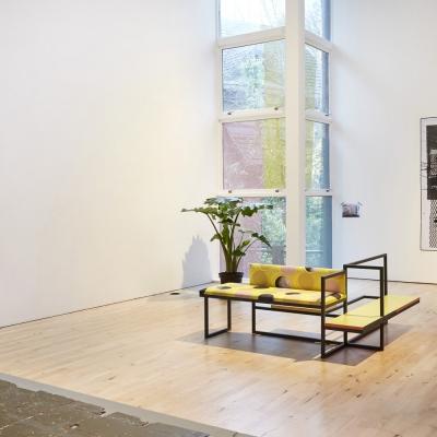 """Céline Condorelli, """"Average Spatial Compositions"""", 2017, widok instalacji, Prologue, Stanley Picker Gallery (Kingston), fot. Corey Bartle-Sanderson, dzięki uprzejmości artystki: Fotografia prezentuje fragment widoku wystawy. Na pierwszym planie widnieje obiekt przypominający mebel. Na drugim planie można dostrzec fotografie umieszczoną na ścianie."""