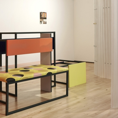 """Céline Condorelli, """"Average Spatial Compositions"""", 2015, installation view, Prologue, Stanley Picker Gallery (Kingston), photograph by Corey Bartle-Sanderson, courtesy of the artist.: The photo shows the view of the exhibition. In the central part of the view, there is an object resembling a piece of furniture. In the visible space on the white walls, there are colorful artworks combining photographs with geometry."""