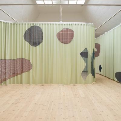 """Céline Condorelli, """"Host"""", 2019, widok instalacji, Kunsthal Aarhus (Aarhus), fot. Mikkel Kaldal, dzięki uprzejmości artystki: Fotografia prezentuje wielkoformatową kurtynę w kolorze jasnej zieleni. Materiał spełnia funkcję podłoża na którym wyświetlane są filmy tematyczne. Kurtyna mierzy ponad 30 metrów długości i składa się z czterech sekcji, które umożliwiają różne konfiguracje. Półprzezroczyste okna umożliwiają widok na całą przestrzeń oraz odbywające się wystawy lub wydarzenia."""
