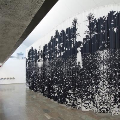 """Céline Condorelli, """"White Gold"""", 2012, widok instalacji, Lunds Konsthall (Sweden), fot. Terje Östling, dzięki uprzejmości artystki: Fotografia przestawia fragment widoku wystawy prezentujący bawełnianą zasłonę z naniesionym nadrukiem cyfrowym. Achromatyczna tkanina zawiera przedstawienia dotyczące przemysłu tekstylnego oraz fragmenty historii kolonialnej, handlu międzynarodowego, pracy, polityki wojowniczej, a wraz z nimi warunki istnienia kurtyny. Całość stanowi wizualną historię w układzie pionowym."""