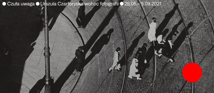 Zdjęcie jest zrobione z lotu ptaka. Na czarno-białej fotografii widać ludzi, którzy przechodzą przez ulicę. W prawym dolnym rogu znajduje się duża, pomarańczowa kropka.