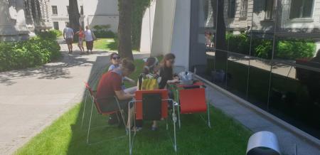 Prezentacje portalu Zasoby.: Cztery osoby siedzą przy komputerze w ogrodzie ms1. Komputer stoi na małym biurku. Pracowniczka muzeum prezentuje gościom portal zasoby.msl.org.pl