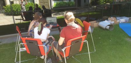Prezentacje rocznego dorobku digitalizacyjnego na portalu zasoby.msl.org.pl : Cztery osoby siedzą przy komputerze w ogrodzie ms1. Komputer stoi na małym biurku. Pracowniczka muzeum prezentuje gościom portal zasoby.msl.org.pl
