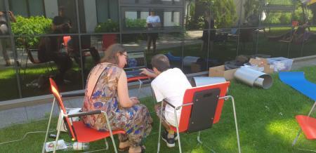 Prezentacje portalu zasoby.: Dwie osoby siedzą przy komputerze w ogrodzie ms1. Komputer stoi na małym biurku. Pracowniczka muzeum prezentuje gościom portal zasoby.msl.org.pl